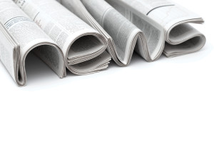 Stacks of modern newspapers, composed in form of word NEWS on white background